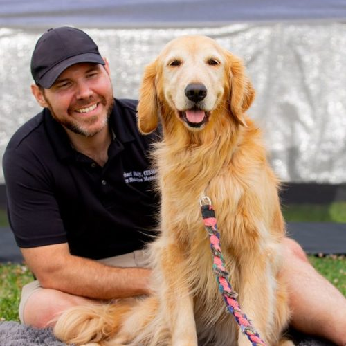 Michael Daly posing posing with happy dog client after another successful canine massage session