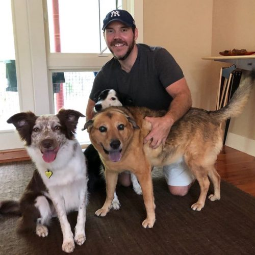 Michael Daly, Certified Canine Massage Therapist, posing with three happy dog clients