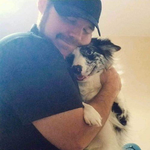 Michael hugging a happy canine client after completion of another pet massage